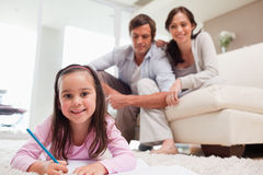 Girl drawing with her parents in the background Stock Photography