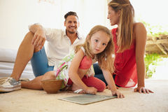 Girl drawing with her parents in living room Royalty Free Stock Image