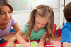 Girl drawing with her teacher stock images