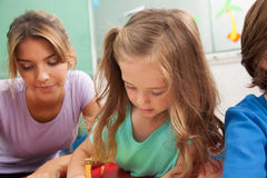 Girl drawing with her teacher stock photography