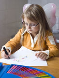 Girl drawing at home. A young angel girl drawing a picture, a set of felt tips on the table stock photos
