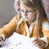Girl drawing at home. A young angel girl drawing a picture, a set of felt tips on the table stock images