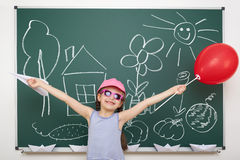 Girl drawing home and garden on school board Stock Photo
