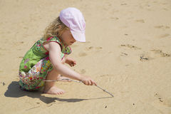 Girl Drawing On White Beach With Stick Stock Images