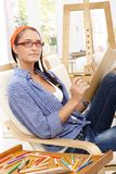Girl with drawing pad. Artistic girl sitting with drawing pad in armchair, working, looking up stock photos