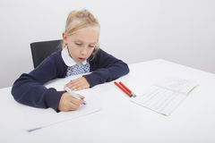 Girl drawing on paper with felt tip pen at table Stock Photography