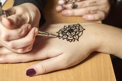 Girl drawing patterns by henna on the hands royalty free stock images