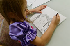 Girl drawing with pencil. Girl in purple dress seated at desk making a pencil drawing on white paper of a young girl with plaits royalty free stock photo