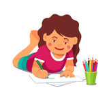 Girl drawing with pencils lying on the floor Stock Image