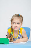 The girl drawing with pencils at the table looked left Stock Photos