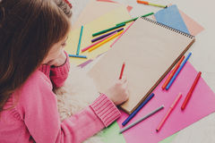Girl drawing picture with colored pencils and Royalty Free Stock Photo