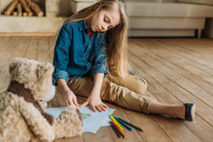 Girl drawing picture on floor at home, kids drawing concept Stock Photography