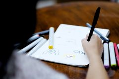 A girl drawing a picture on white paper by black pen