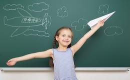 Girl drawing plane on school board Royalty Free Stock Photos