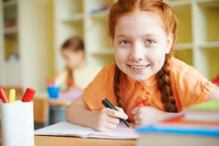 Girl drawing. Portrait of lovely girl drawing at workplace at lesson royalty free stock photos