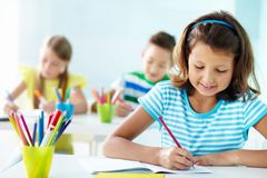 Girl drawing. Portrait of lovely girl drawing at workplace with schoolmates on background royalty free stock photo