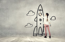 Girl drawing rocket. Young student girl standing with back and drawing rocket royalty free stock photo