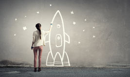 Girl drawing rocket. Young student girl standing with back and drawing rocket Royalty Free Stock Images