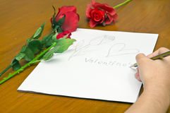 A girl is drawing a rose on a pile of paper. For Valentine's event royalty free stock photography