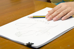 A girl is drawing a rose on a pile of paper. For Valentine's event royalty free stock images