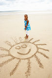 Girl drawing in sand Royalty Free Stock Photos