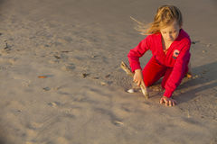 Girl Drawing in Sand Stock Images