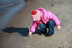 A girl drawing on the sand Stock Images