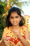 Girl drawing sticky bubblegum thread. A small Indian girl stretching a bubble gum thread from the mouth Stock Photo