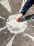 Girl drawing a sun with colored chalk on pavement Royalty Free Stock Image