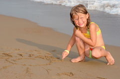 Girl drawing sun on sand Royalty Free Stock Photos