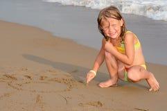 Girl drawing sun on sand Royalty Free Stock Photos