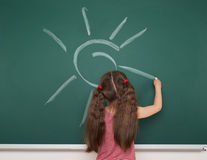 Girl drawing sun on school board Royalty Free Stock Images