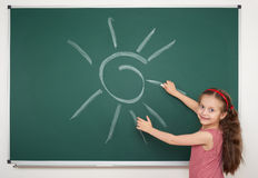 Girl drawing sun on school board Royalty Free Stock Photography