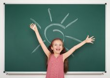 Girl drawing sun on school board Stock Images