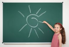Girl drawing sun on school board Royalty Free Stock Photo