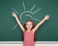 Girl drawing sun on school board Stock Image