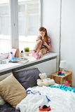 Girl drawing on window sill. Concentrated little girl sitting on wide window sill in her comfortable bedroom and drawing in notepad royalty free stock photo