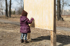 Girl drawing on a wooden board Royalty Free Stock Images