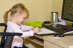 Girl drawing at work station. Pretty smiling young blond girl writing or drawing while sitting at computer work station stock images