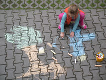 Girl drawing. Young girl drawing with crayons on the courtyard Royalty Free Stock Photos