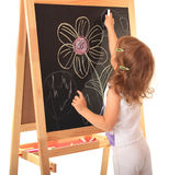 Girl draws. A little girl draws a chalk on a board Royalty Free Stock Images