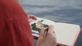 Girl draws in an album, a beautiful drawing on the seashore