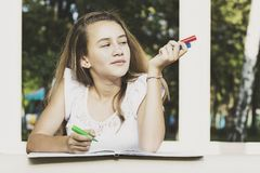 Girl draws on the album Stock Photos