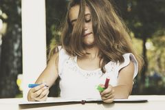 Girl draws on the album Royalty Free Stock Photo