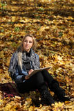 The girl draws in the autumn park Stock Image