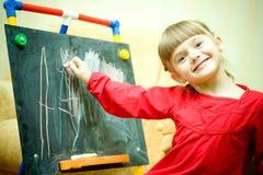 Girl draws on the blackboard Royalty Free Stock Image