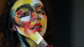 Girl draws on the brush in the paint itself stock video footage