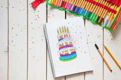 The girl draws a cake with bright colored markers. Gifts, rosettes, confetti and festive accessories. royalty free stock photo
