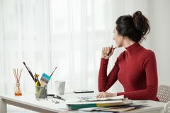 The girl draws on canvas. artist`s workplace. Girl in red clothes is sitting in the office. One Young Woman Only. Artist`s Model Royalty Free Stock Photo