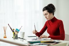 Girl draws on canvas in a bright office. Artist`s model. Artist`s workplace, one young woman only, mascara brush. girl painter working in the office Royalty Free Stock Photo